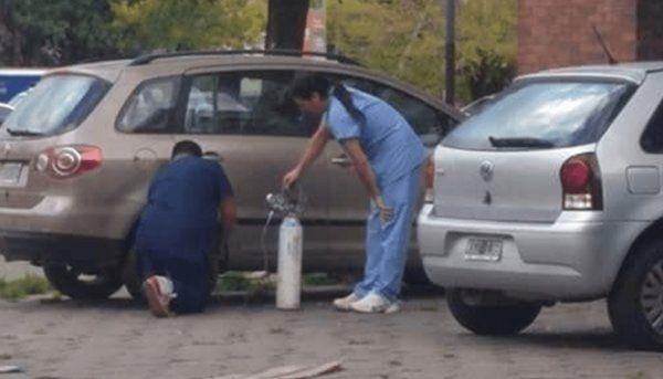 Empelados del hospital Evita utilizan un tubo de oxígeno para inflar neumático
