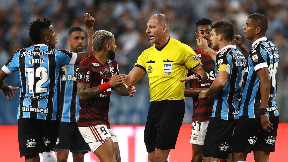Pitana trata de calmar a los jugadores de ambos equipos.